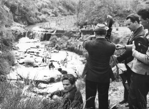 Pasolini (seated) on the set of THE GOSPEL ACCORDING TO SAINT MATTHEW, prior to filming John's baptizing of Jesus.
